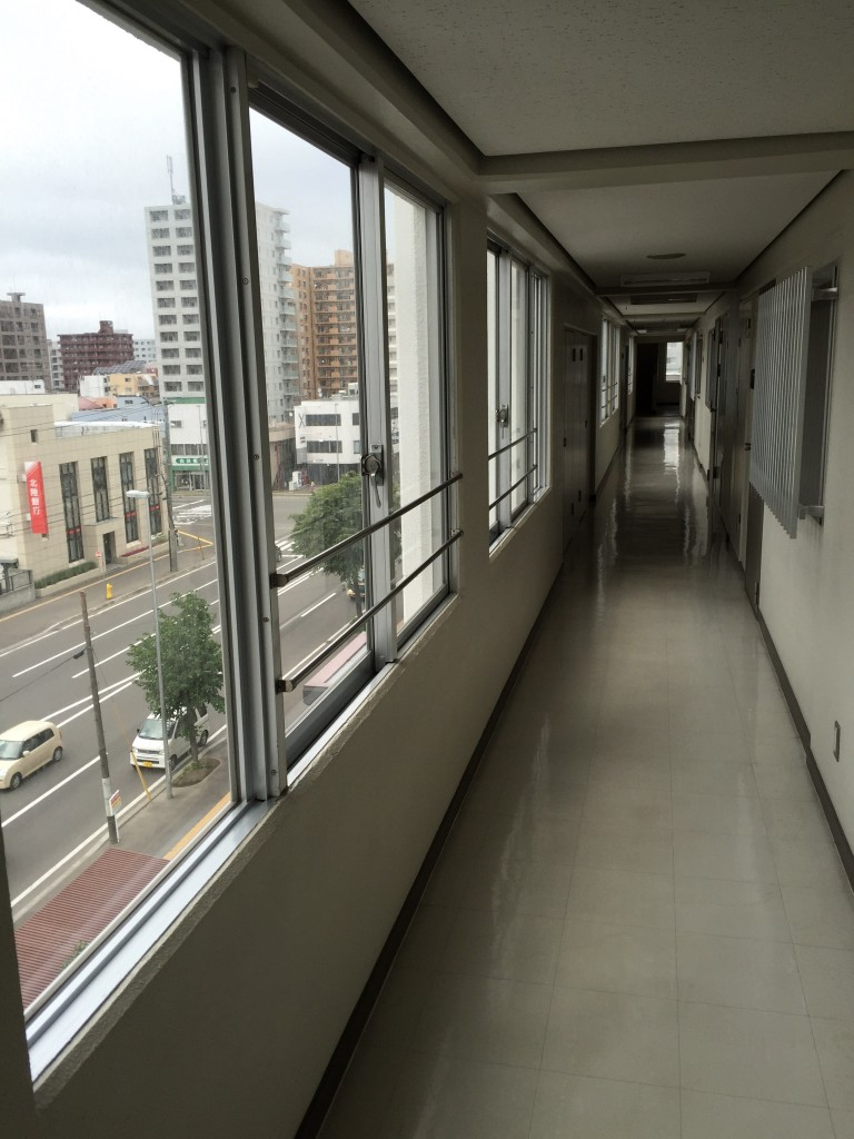 The hallway coming from the stairs/elevator to his door, in front of which I am standing. It's the 5th floor of a 14 story building.  Japan has some impressive vertical density.