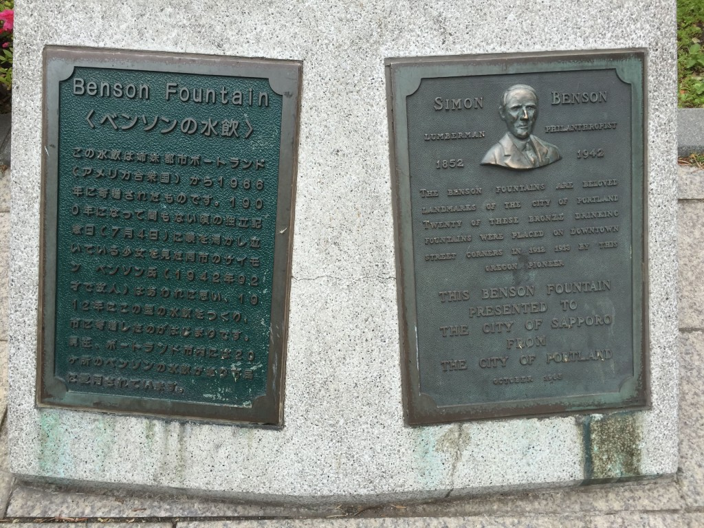 A plaque commemorating Sapporo and Portland as sister cities and celebrating an exchange of bronze drinking fountains, next to one that didn't work.