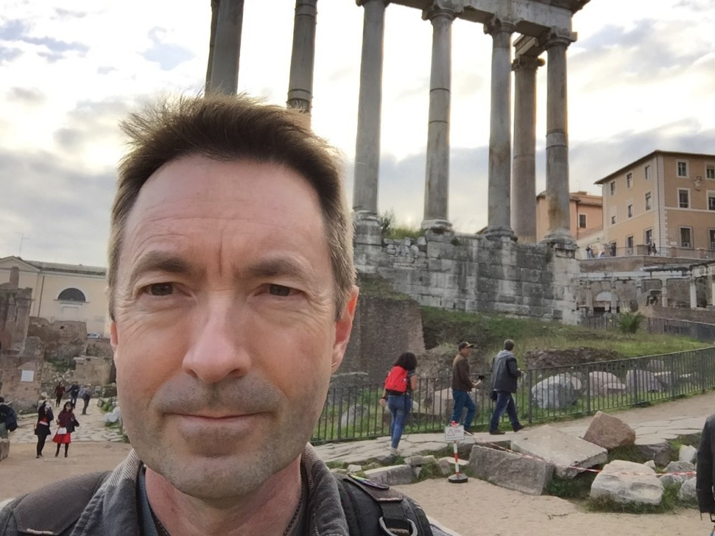 "A rare selfie. This started out as an accident: I was trying to take a picture of the thing I was facing, had brushed the ""flip camera"" button, and found I was taking a selfie. So I thought, what the hell, one can't hurt. So, it's now ""me and the Temple of Saturn""."