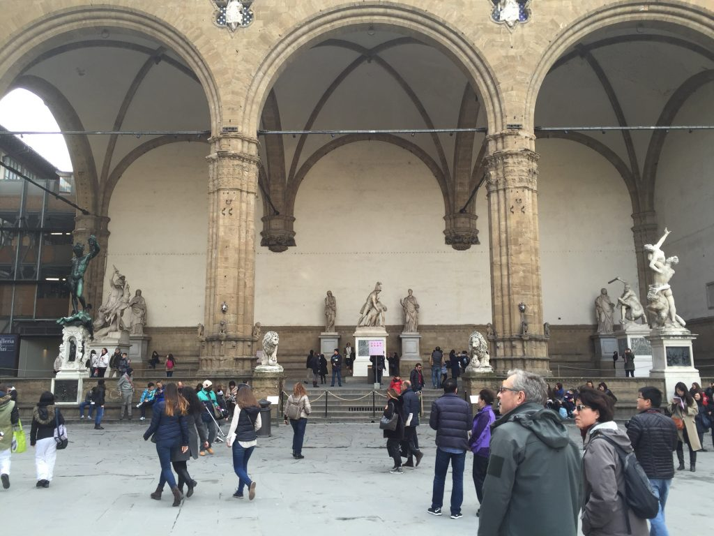 The Loggia Dei Lanzi. Lucy recovers on the stone benches at the back, while George goes back out to fetch the photographs that she dropped. (Which have blood on them, despite her not actually having been anywhere near the stabbing. Italian blood, very energetic.)