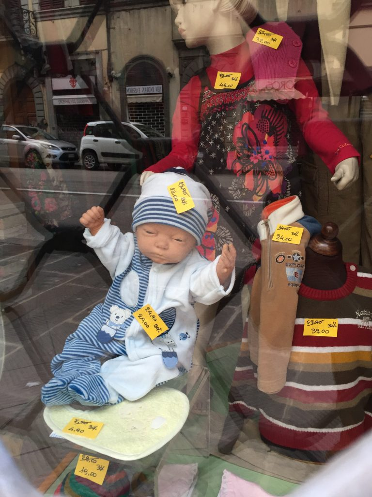 OMG! I took this picture because of how creepy the doll looked, and I only just now properly registered their expressions: this window display is basically every Madonna and Child ever! (Surely not intentional.)