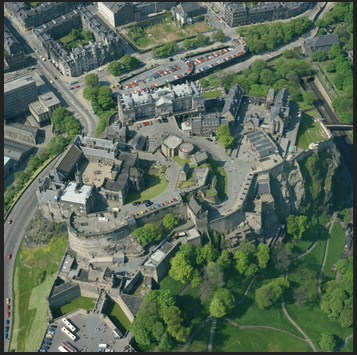 You come in through the main gate at the bottom of the picture (the northeast corner), follow the road up and to the right, curve around past the outbuildings and prison, back into an inner courtyard with ancient chapel and battlements, and then reach the square of the household buildings on the left.
